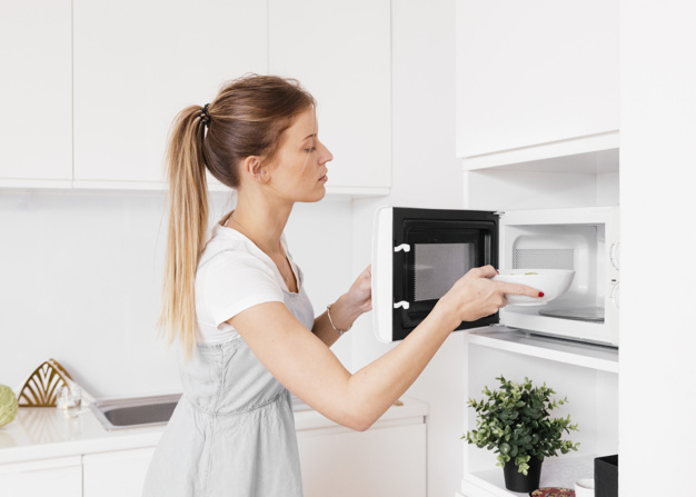 nő ételt melegít a mikrohullámú sütőben