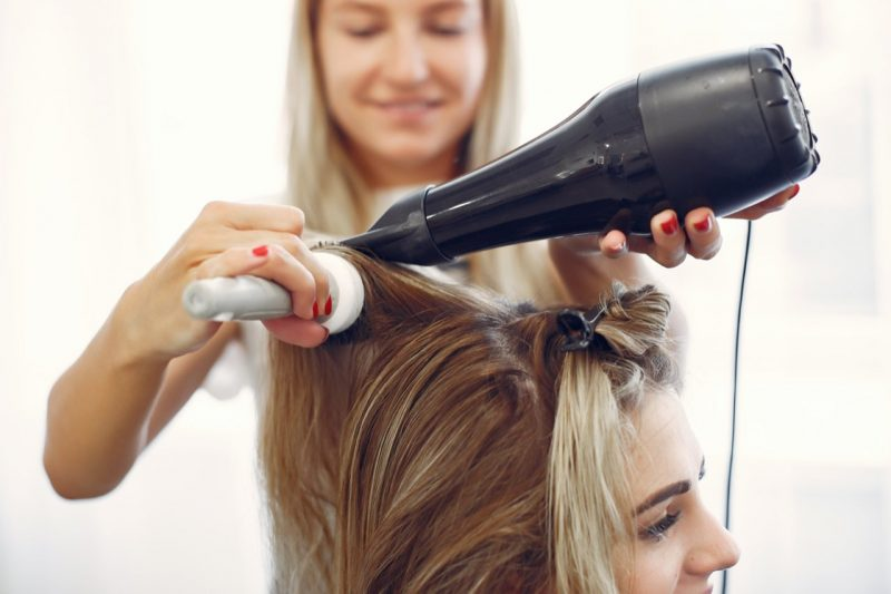 nő hajat szárít hajszárítóval